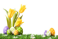 Uova di Pasqua che si nascondono nell'erba con i tulipani Immagine Stock