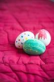 Uova di Pasqua che si trovano su un fondo rosso Immagine Stock Libera da Diritti