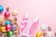 Uova di Pasqua colorate con le orecchie ed i dolci di coniglio il piano pone con spazio per progettazione, composizione orizzonta immagini stock libere da diritti