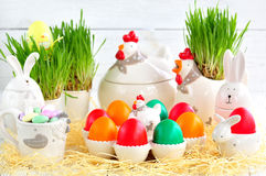 Uova di Pasqua colorate con le pitture ed il piatto organici sotto forma di polli e di conigli su un fondo di legno bianco Fotografia Stock