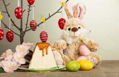 Uova di Pasqua colorate, coniglietto, dessert del formaggio di Pasqua, fiori sul gr Fotografia Stock Libera da Diritti