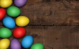 Uova di Pasqua colorate su fondo di legno scuro Fondo scuro rustico Uova di Pasqua variopinte su una tavola di legno, decorazione fotografia stock