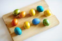 Uova di Pasqua colorate sulla tavola bianca sul giorno di Pasqua Immagine Stock