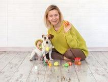 Uova di Pasqua di colore del cane e della donna Fotografia Stock