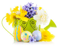 Uova di Pasqua con i fiori della molla in annaffiatoio immagini stock libere da diritti
