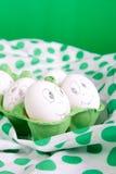 Uova di Pasqua con i fronti divertenti nel verde Immagine Stock