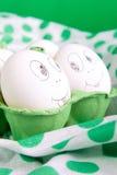 Uova di Pasqua con i fronti divertenti nel verde Fotografie Stock Libere da Diritti
