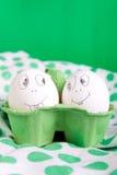 Uova di Pasqua con i fronti divertenti nel verde Immagini Stock