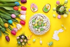 Uova di Pasqua con i tulipani variopinti su fondo giallo Concetto di festa di Pasqua Decorazione di Pasqua fotografia stock