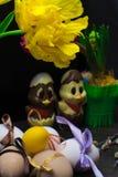 uova di Pasqua con il nastro di colore ed il pollo sveglio del cioccolato decorati con il fiore - tulipano e geocint Fotografie Stock Libere da Diritti