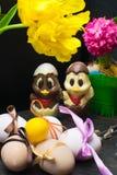 uova di Pasqua con il nastro di colore ed il pollo sveglio del cioccolato decorati con il fiore - tulipano e geocint Immagini Stock Libere da Diritti