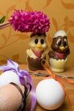 uova di Pasqua con il nastro di colore ed il pollo sveglio del cioccolato decorati con il geocint del fiore fresco su fondo aranc Fotografia Stock
