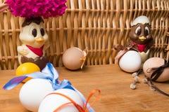 uova di Pasqua con il nastro di colore ed il pollo sveglio del cioccolato decorati con il geocint del fiore fresco su fondo aranc Fotografia Stock Libera da Diritti