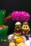 uova di Pasqua con il nastro di colore ed il pollo sveglio del cioccolato decorati con il geocint del fiore su fondo nero Fotografia Stock