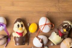 uova di Pasqua con il nastro di colore ed il pollo sveglio del cioccolato sui precedenti arancio Fotografia Stock