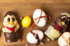 uova di Pasqua con il nastro di colore ed il pollo sveglio del cioccolato sui precedenti arancio Fotografia Stock Libera da Diritti
