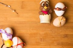 uova di Pasqua con il nastro di colore ed il pollo sveglio del cioccolato sui precedenti arancio Immagine Stock Libera da Diritti