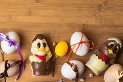 uova di Pasqua con il nastro di colore ed il pollo sveglio del cioccolato sui precedenti arancio Immagine Stock