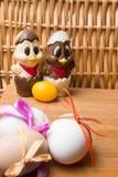 uova di Pasqua con il nastro di colore ed il pollo sveglio del cioccolato sui precedenti arancio Immagini Stock
