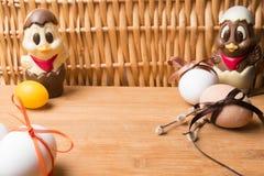 uova di Pasqua con il nastro di colore ed il pollo sveglio del cioccolato sui precedenti arancio Fotografie Stock