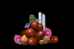 Uova di Pasqua con le pasticcerie e le candele su un fondo nero Fotografie Stock