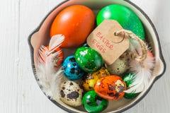 Uova di Pasqua con le piume sulla pentola sulla tavola bianca Fotografia Stock Libera da Diritti