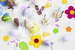 Uova di Pasqua, coniglietti, fiori e decorazioni delle piume Immagini Stock