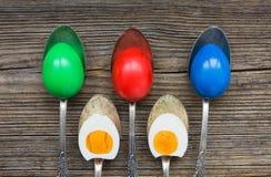 Uova di Pasqua in cucchiai su fondo di legno fotografia stock