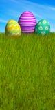 Uova di Pasqua decorate nell'erba sotto un cielo blu Fotografia Stock Libera da Diritti