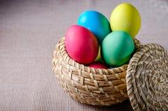 Uova di Pasqua dei colori differenti in un canestro di vimini Fotografia Stock Libera da Diritti