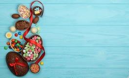 Uova di Pasqua del cioccolato, nastri variopinti e dolci su un fondo blu Immagini Stock Libere da Diritti