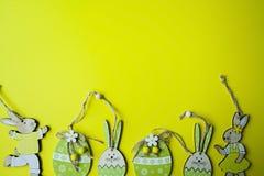 Uova di Pasqua del coniglietto di pasqua e su un fondo giallo Vista da sopra copi lo spazio, spazio per testo immagine stock libera da diritti