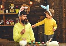 Uova di Pasqua della pittura del bambino e del padre fotografia stock libera da diritti