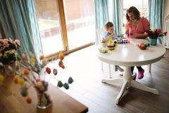 Uova di Pasqua della pittura del figlio e della madre Fotografia Stock