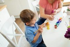 Uova di Pasqua della pittura del figlio e della madre Immagine Stock