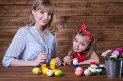 Uova di Pasqua della pittura della figlia e della mamma immagini stock