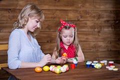 Uova di Pasqua della pittura della figlia e della mamma immagine stock libera da diritti