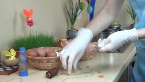 Uova di Pasqua della pittura facendo uso delle coperture della cipolla e del calzino stock footage