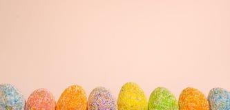 Uova di Pasqua di fila con il fondo rosa-chiaro della molla fotografie stock libere da diritti