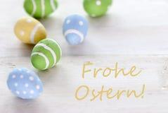 Uova di Pasqua di giallo e di verde blu con i mezzi tedeschi Pasqua felice di Frohe Ostern del testo Fotografia Stock Libera da Diritti