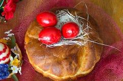 Uova di Pasqua di legno rosse sulla pagnotta Immagini Stock Libere da Diritti