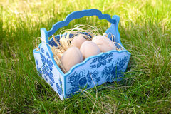 Uova di Pasqua di legno in un canestro blu Fotografia Stock
