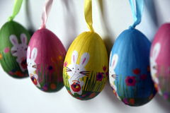 Uova di Pasqua di plastica ansimate Colourful con i coniglietti bianchi in una fila Immagine Stock