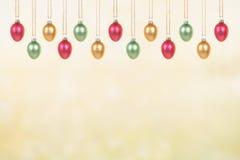Uova di Pasqua di vetro decorative che appendono su un fondo giallo verde della molla Immagini Stock Libere da Diritti