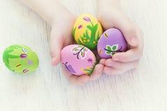 Uova di Pasqua dipinte con le immagini della molla in mani di un bambino Fotografia Stock Libera da Diritti