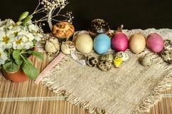 Uova di Pasqua dipinte ed uova di quaglia, pasticcerie, un vaso della viola bianca su un tappeto della paglia Immagine Stock Libera da Diritti