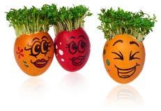 Uova di Pasqua dipinte a mano con i fronti sorridenti felici divertenti con i cres Fotografia Stock