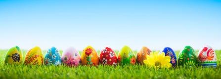 Uova di Pasqua dipinte a mano variopinte su erba Insegna, panoramica immagini stock