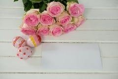 Uova di Pasqua dipinte, mazzo di fiore e busta su fondo di legno Immagini Stock Libere da Diritti