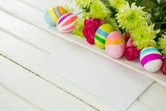 Uova di Pasqua dipinte, mazzo di fiore e busta su fondo di legno Fotografia Stock